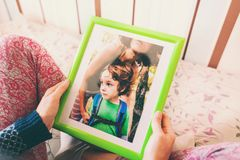 A woman looks at a photo. A women looks at a photo of a boy. Mom holds a photo frame with a photograph of her son. A small child and memories Royalty Free Stock Images