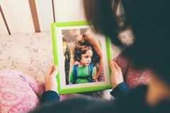 A woman looks at a photo. A women looks at a photo of a boy. Mom holds a photo frame with a photograph of her son. A small child and memories Royalty Free Stock Photo