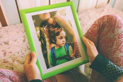 A woman looks at a photo. A women looks at a photo of a boy. Mom holds a photo frame with a photograph of her son. A small child and memories Stock Images