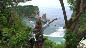 Woman looks at picturesque landscape and rise hands. Atuh beach, Nusa Penida island. Popular travel destination on Bali holidays. Indonesia stock video footage