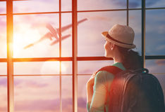 Woman looks at a plane. Young beautiful woman looks at a plane at the airport Royalty Free Stock Image
