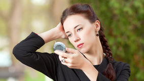The woman looks in a pocket mirror stock photography