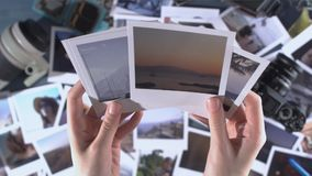 A woman looks at printed photos from travel with sea, sun, palm, mountains spread on a wooden table with photo camera. And lens stock footage