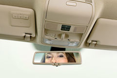 Woman looks on the rear-view mirror. Young woman sits on driver's seat and looks in the rear-view mirror royalty free stock photos