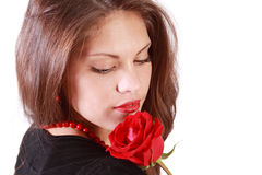 Woman looks at red rose on her shoulder Royalty Free Stock Photography