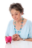 Woman looks sadly at savings - elder woman isolated on white bac Royalty Free Stock Photo