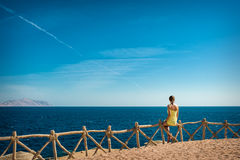 Woman looks at the sea and the island of Tiran Royalty Free Stock Image