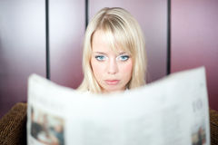 Woman looks shocked. Young blond woman looks in a newspaper and is shocked Royalty Free Stock Images