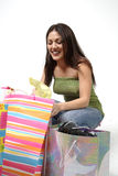 Woman looks through shopping. A young woman squats, looking happy through her bags of shopping Stock Images