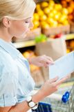 Woman looks through shopping list near the heap of fruits Stock Image