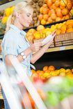 Woman looks through shopping list near the stack of fruits Royalty Free Stock Images