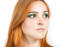 Woman looks sideways, profile. Redheaded girl wearing colorful y Royalty Free Stock Images