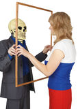 Woman looks at skeleton as reflected Stock Photos