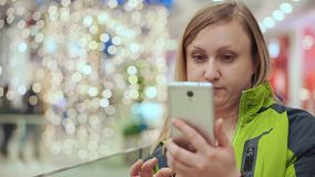 A woman looks into a smartphone in surprise, she is standing in a shopping center, against a background of a light bulb stock footage