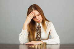 Woman looks on the stacks of gold coins Stock Image