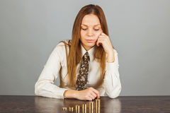 Woman looks on the stacks of gold coins. Young woman looks on the five stacks of gold coins, gray background Royalty Free Stock Images