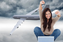Woman looks straight ahead as she celebrates in front of her laptop Stock Photos