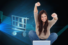 Woman looks straight ahead as she celebrates in front of her laptop Royalty Free Stock Photos