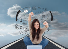 Woman looks straight ahead as she celebrates in front of her laptop Royalty Free Stock Photography
