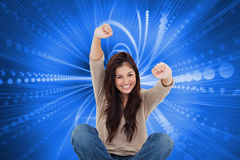 Woman looks straight ahead as she celebrates in front of her laptop Royalty Free Stock Images