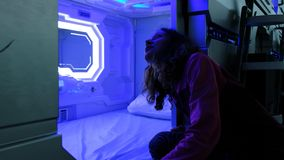 Woman looks with surprise at the Sleepbox with neon lights, the space capsule container for sleeping at the airport.  royalty free stock images
