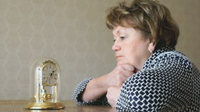 Woman looks at the table clock with pendulum stock video footage