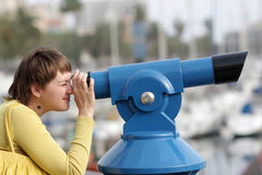 Woman looks through telescope Royalty Free Stock Photo