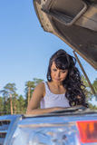 The woman looks thoughtfully at the car engine Stock Photography