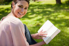 Woman looks to her side while reading a book in the grass Royalty Free Stock Photography