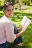 Woman looks to her side while reading a book in a park Royalty Free Stock Images