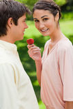 Woman looks to the side while offering a strawberry to her frien Stock Photo