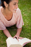 Woman looks to the side while reading a book as she is lying dow Royalty Free Stock Images