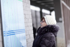 Woman looks at train schedule Stock Photos