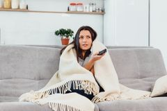 Woman looks TV on the couch. Beautiful woman watching TV fell asleep. stock photography