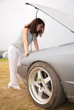 Woman looks under a car cowl Royalty Free Stock Image