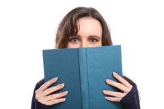 Woman looks up from reading a hard cover book Stock Image