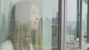 The woman Looks Through a Window. Young pretty blonde woman looks through a window at a city. Happy attractive girl stock video footage