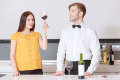 Woman looks at the wine in glass Royalty Free Stock Photo