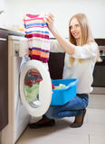 Woman looling  clothes near washing machine Royalty Free Stock Image