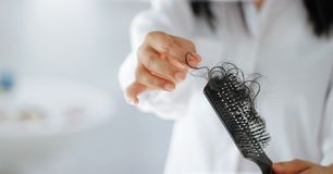 Woman losing hair on hairbrush in hand, soft focus. Woman losing hair on hairbrush in hand , soft focus stock photo