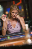 Woman losing at roulette table. In casino stock image