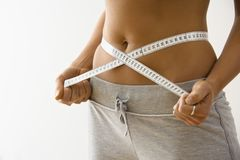 Woman losing weight. Woman standing pulling measuring tape around waist Royalty Free Stock Photo