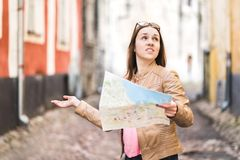 Woman lost in the city. Confused traveler holding map. Royalty Free Stock Photo