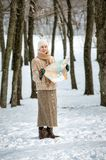 Lost woman with a map. A woman lost in the forest in winter, is seeking her way to home on the map Stock Image