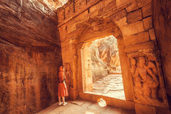 Woman lost in ruins of old city with brick gates. Historical background of India. Royalty Free Stock Images