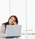 Woman lost in thought with a laptop in front Royalty Free Stock Photography