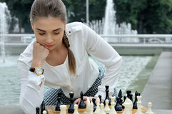 Woman lost in thought over the course of a game of chess Stock Photos