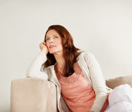 Woman lost in thought while relaxing on couch Stock Images