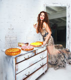 Woman with a lot of various cake pieces. Girl in the dress holding cheesecake Royalty Free Stock Photography