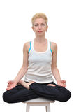 Woman in lotus pose on stool. Woman with blonde short haircut sitting in lotus position on a stool Royalty Free Stock Image